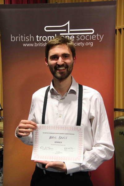 Adam Crighton holding the award for his quartet Aeris Brass by the British Trombone Society